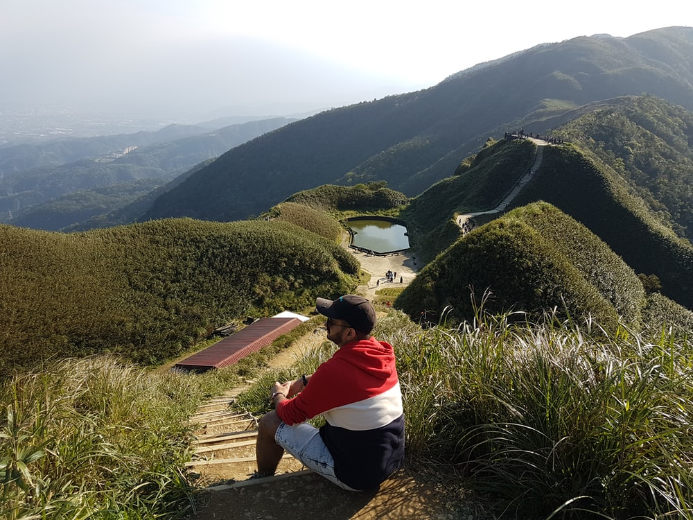 person in red and white hoodie sitting on brown rock looking at green mountains during daytime