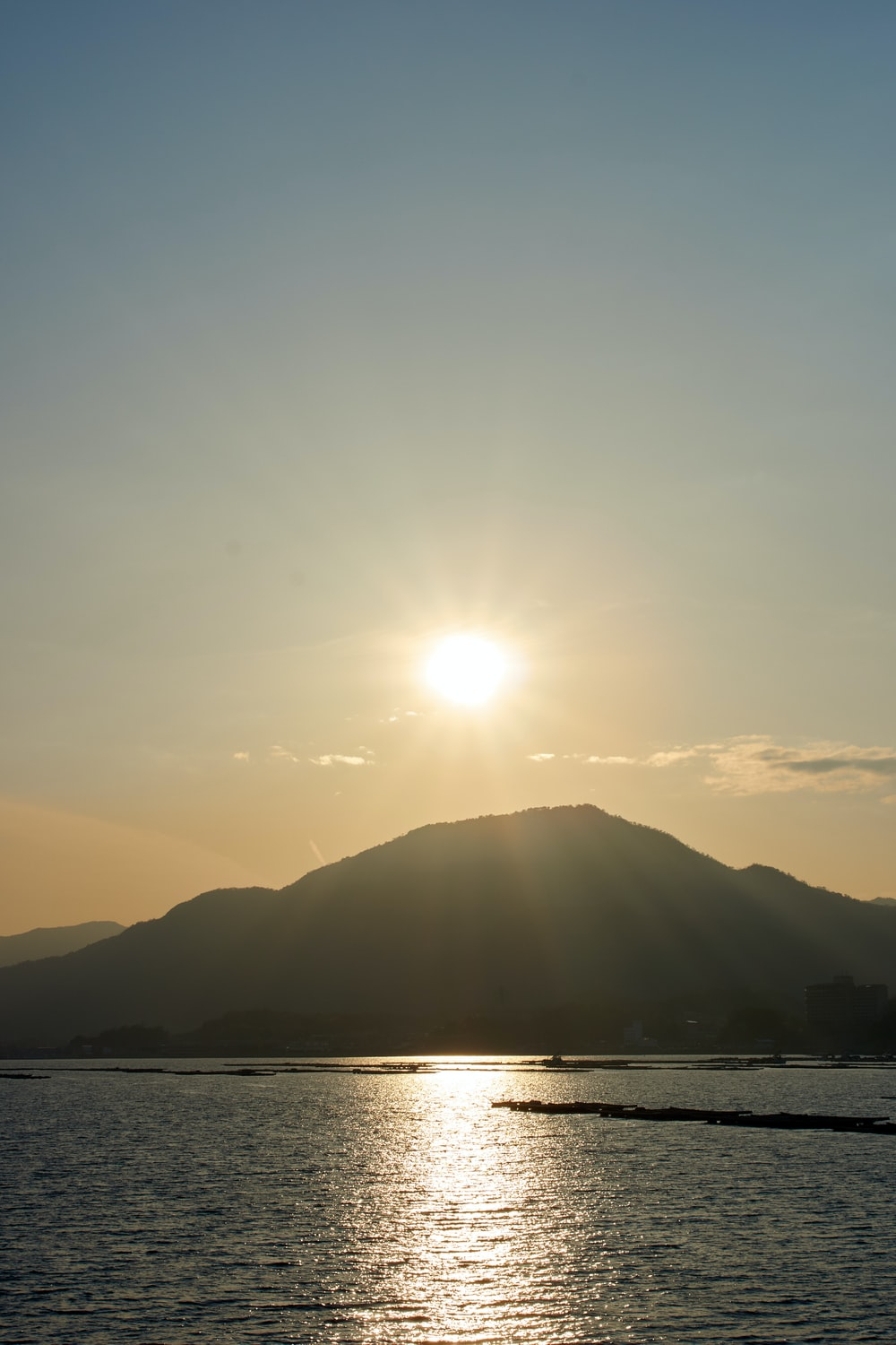 sun over the mountains and body of water