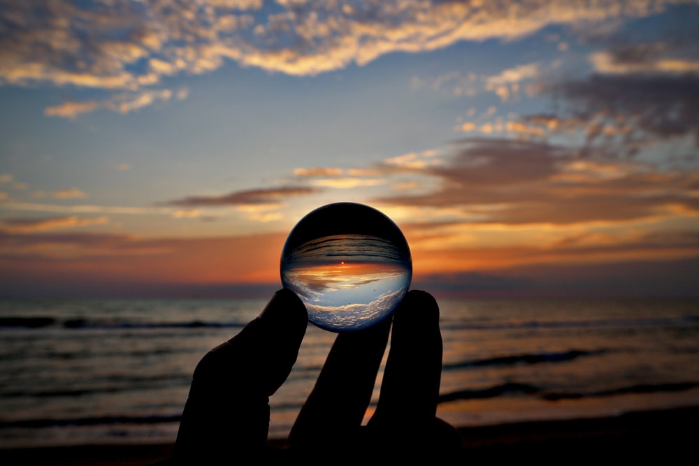 silhouette of person holding clear glass ball during sunset