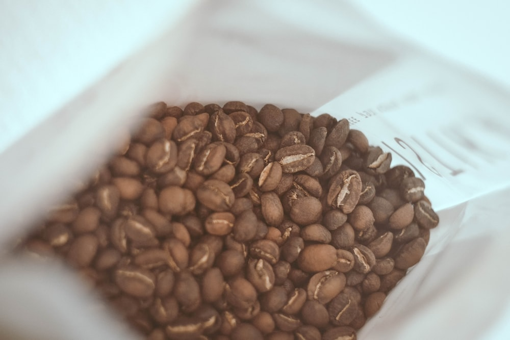 brown coffee beans on white paper