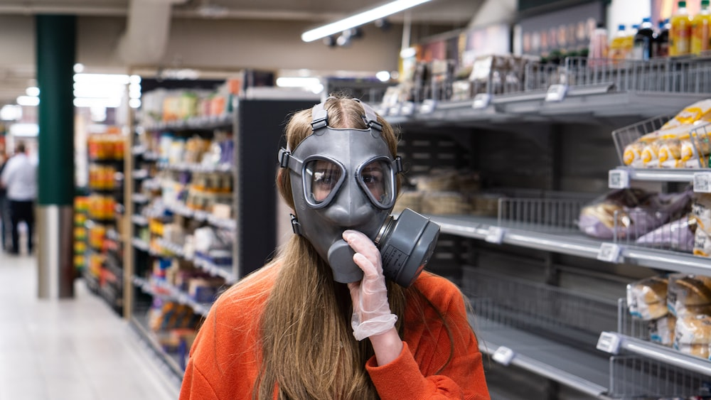 woman in red long sleeve shirt wearing black gas mask