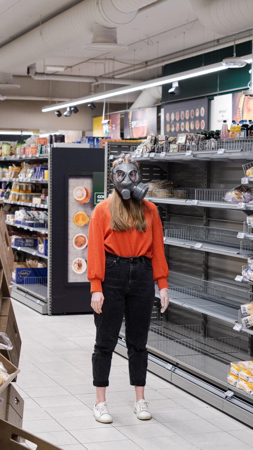 woman in orange jacket and black pants standing in grocery store