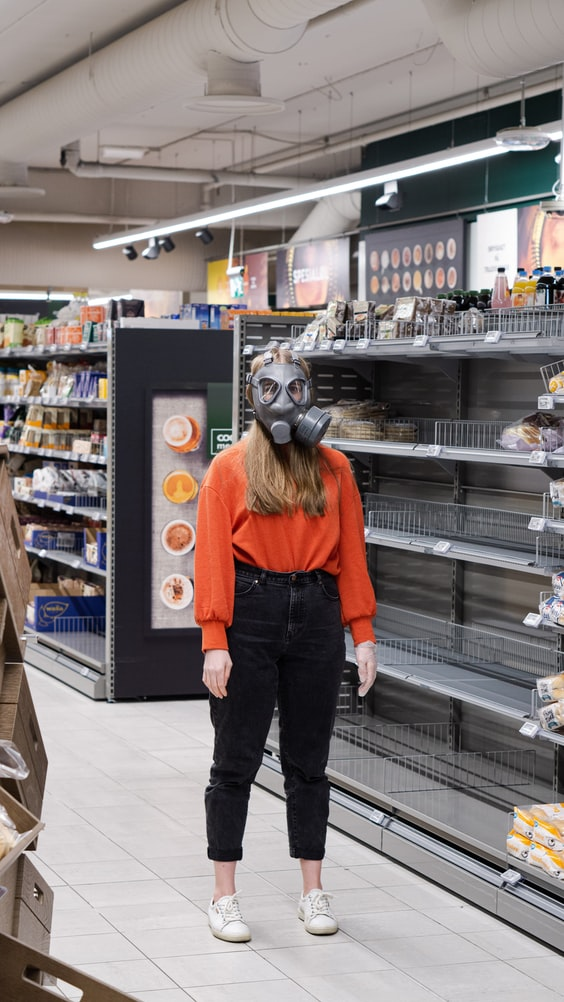 A photo of a woman wearing a gas mask standing next to empty shelves in a grocery store.