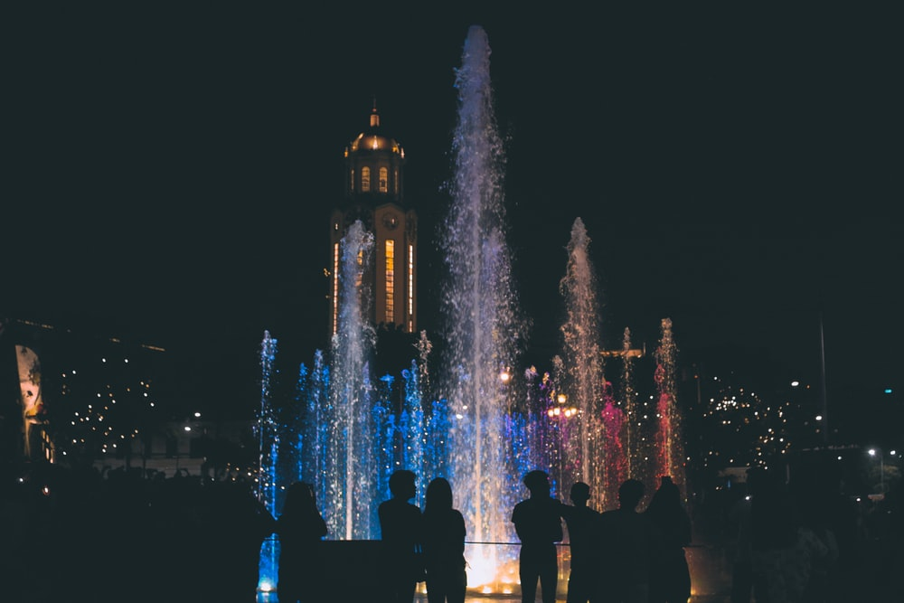 people standing near water fountain during night time