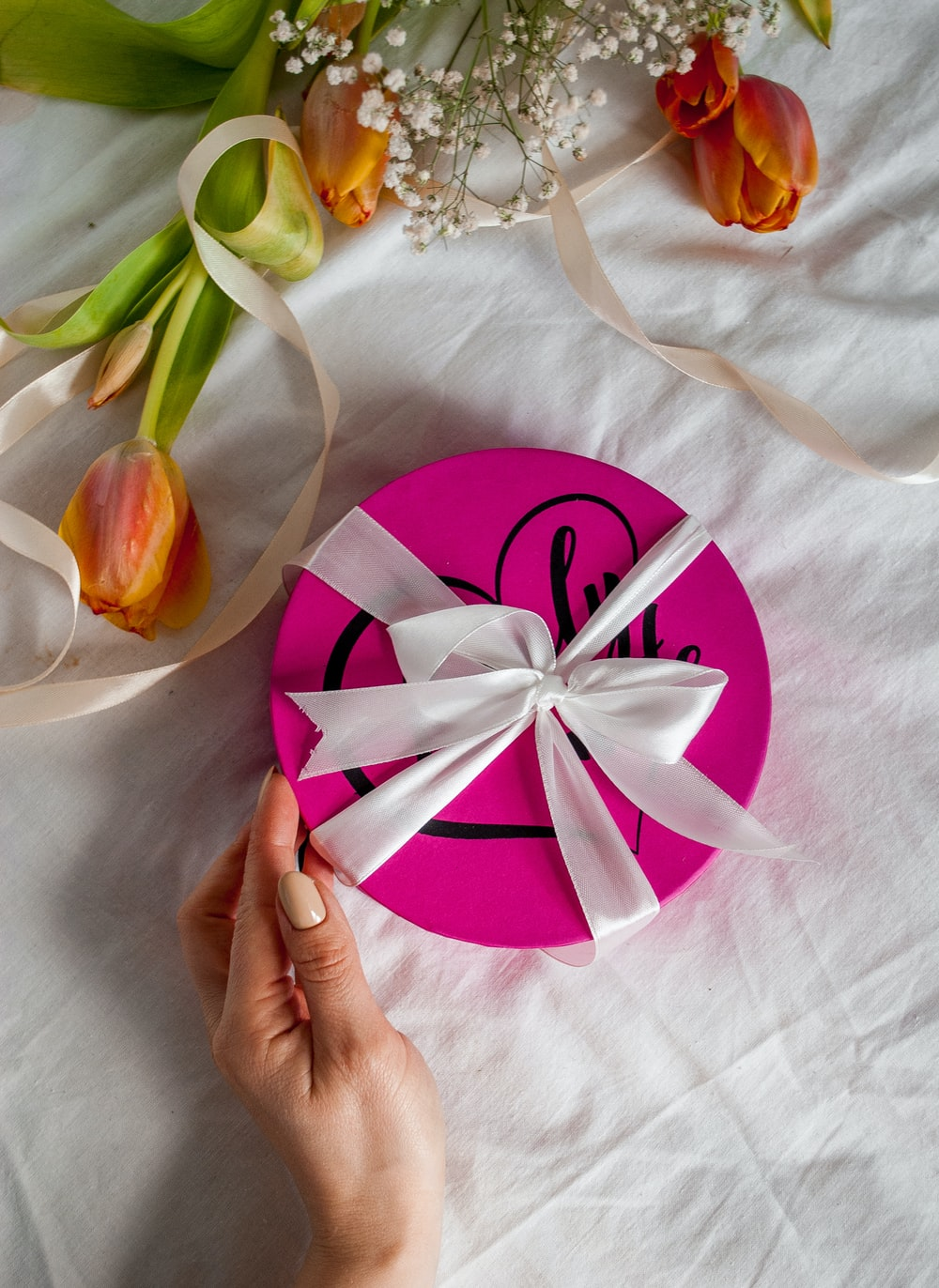 person holding pink and white heart paper