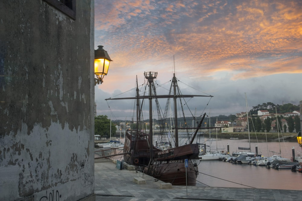 brown and black sail ship on dock during sunset