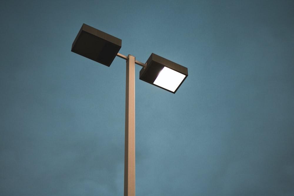 black and white street light under blue sky