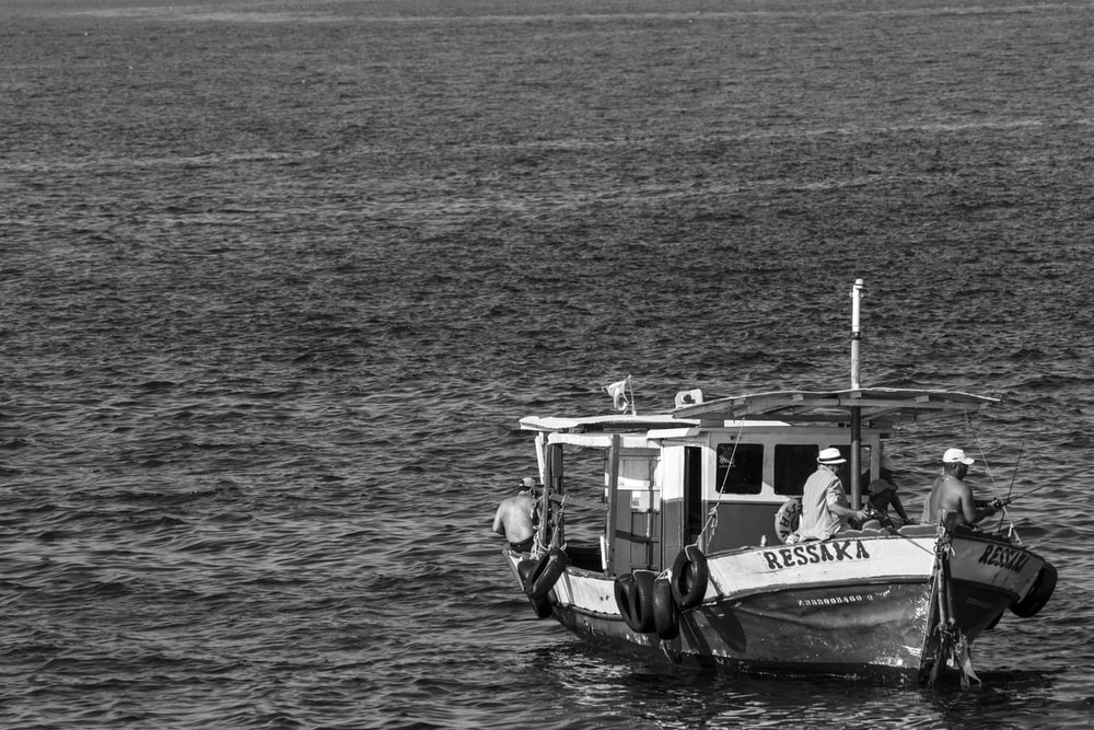 grayscale photo of 2 people riding on boat