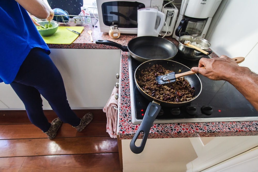 person cooking food on black pan