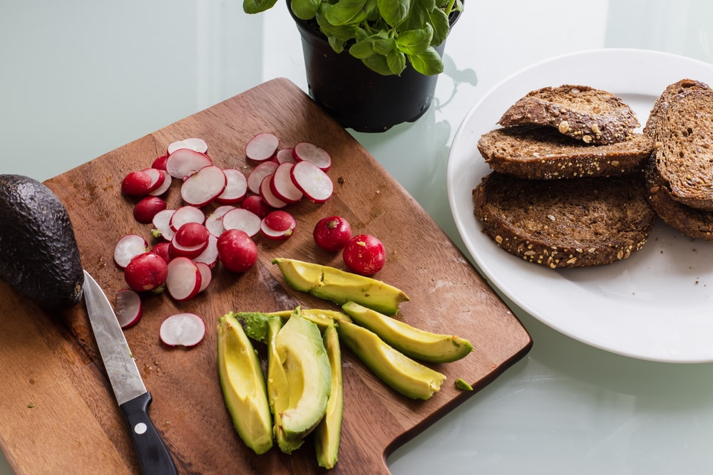 banana fruit and bread on brown wooden chopping board