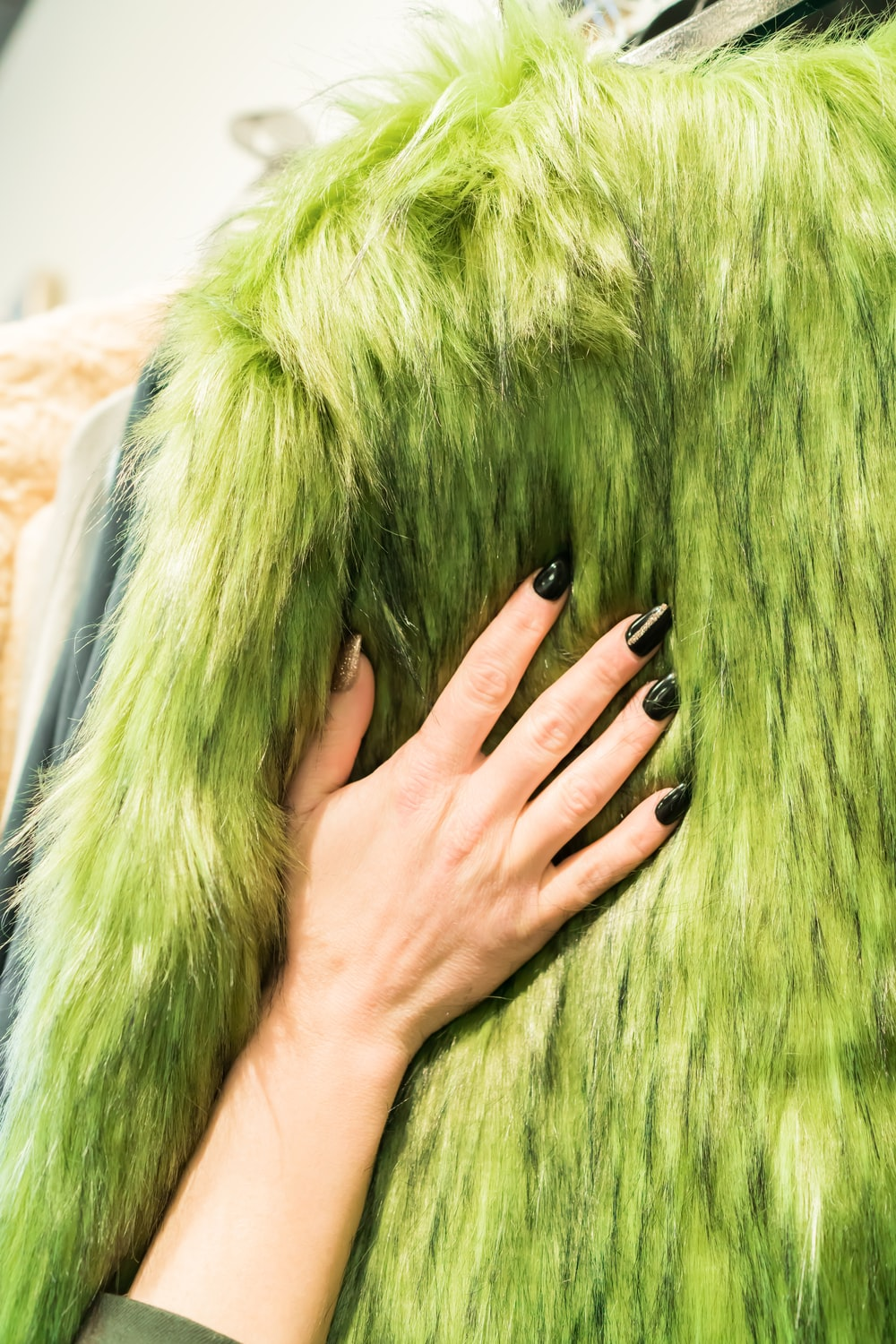 person wearing silver ring on green fur textile