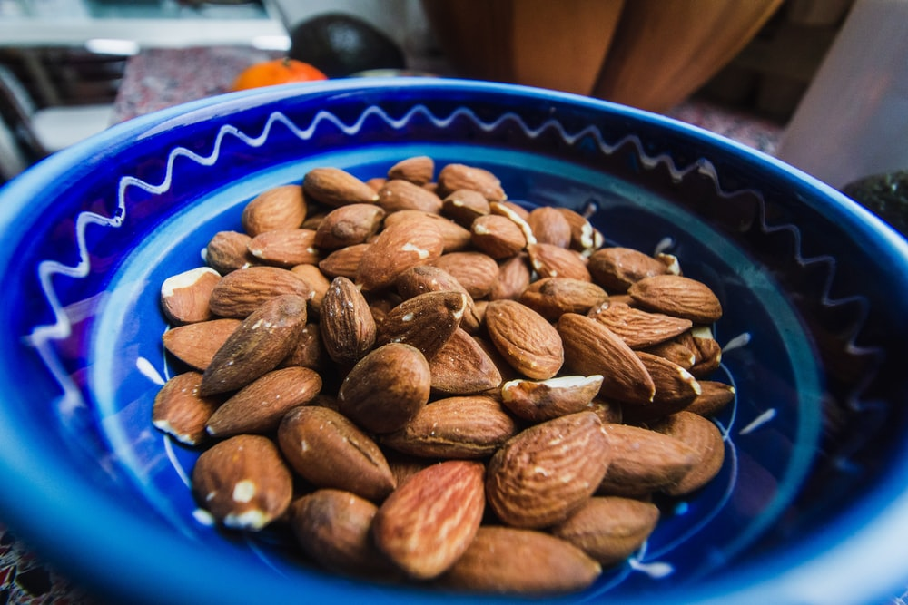 brown almond nuts on blue and white ceramic plate