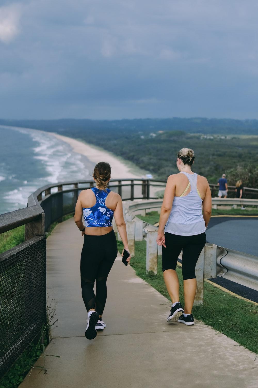 2 women in white tank top and black leggings standing on gray concrete bridge during daytime