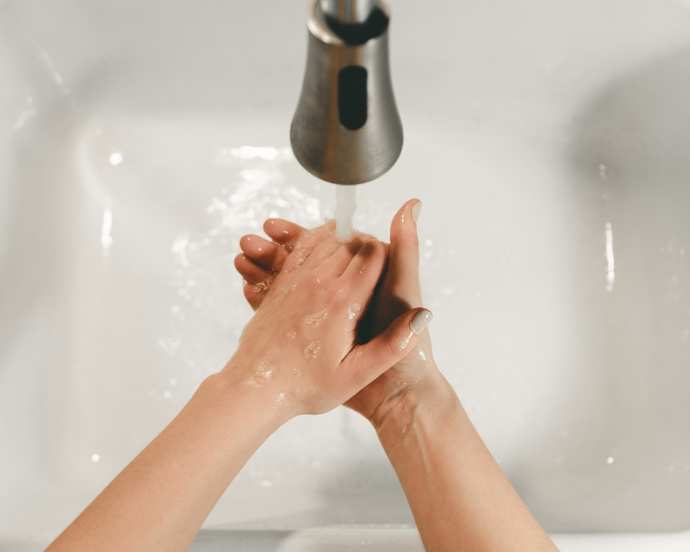 persons feet on white bathtub