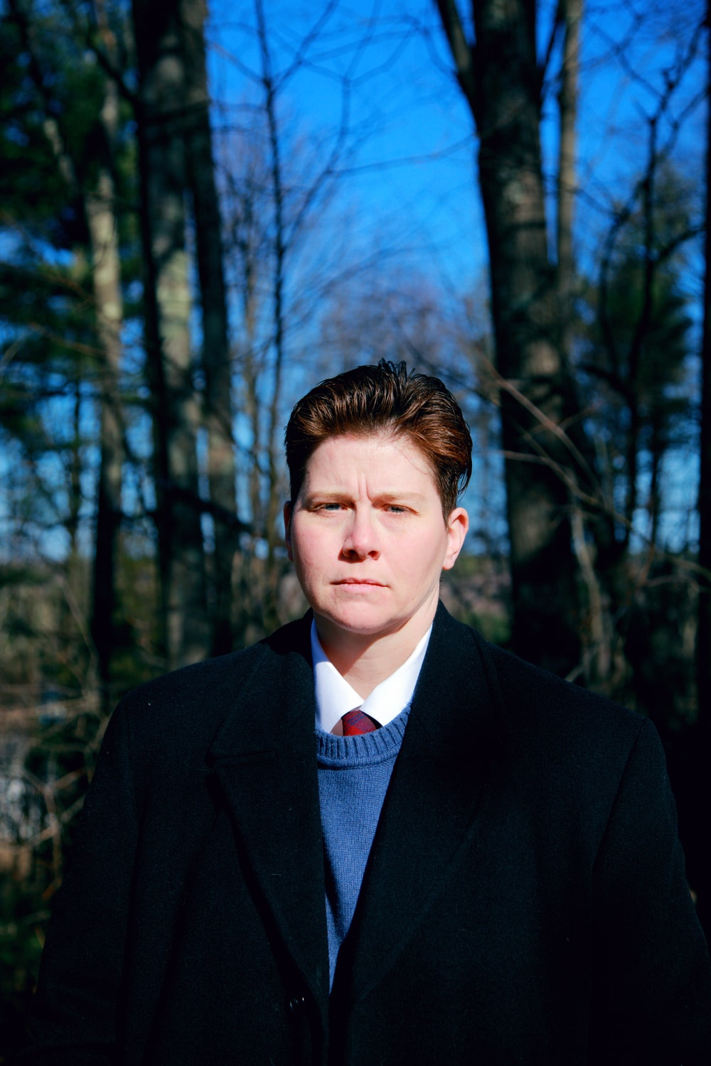 man in black suit jacket standing near trees during daytime