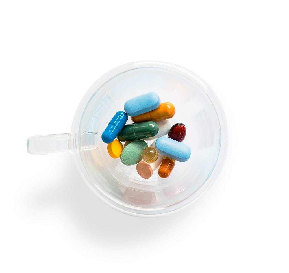 green and white medication pill in clear glass container