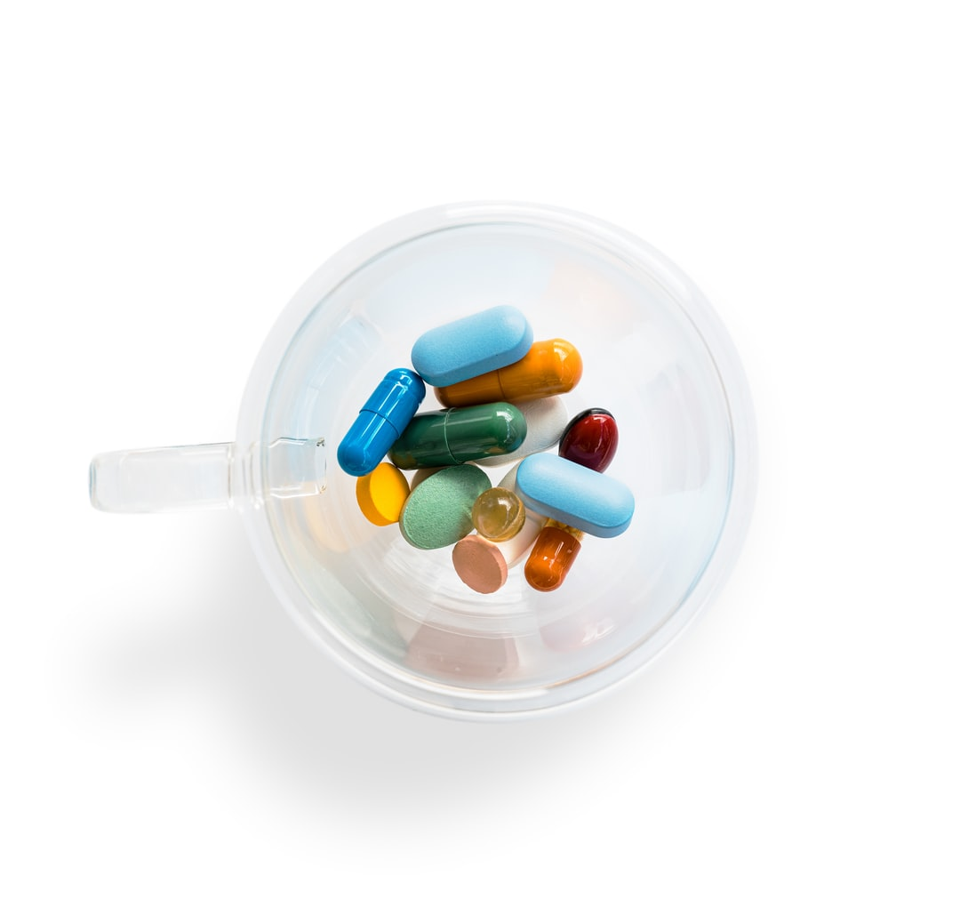 A transparent coffee cup with colourful pills on white background. Dangerous virus. Virus epidemic concept.Tablets,Medicine and healthy. Close up of capsules. Differend kind of pills.Copy space