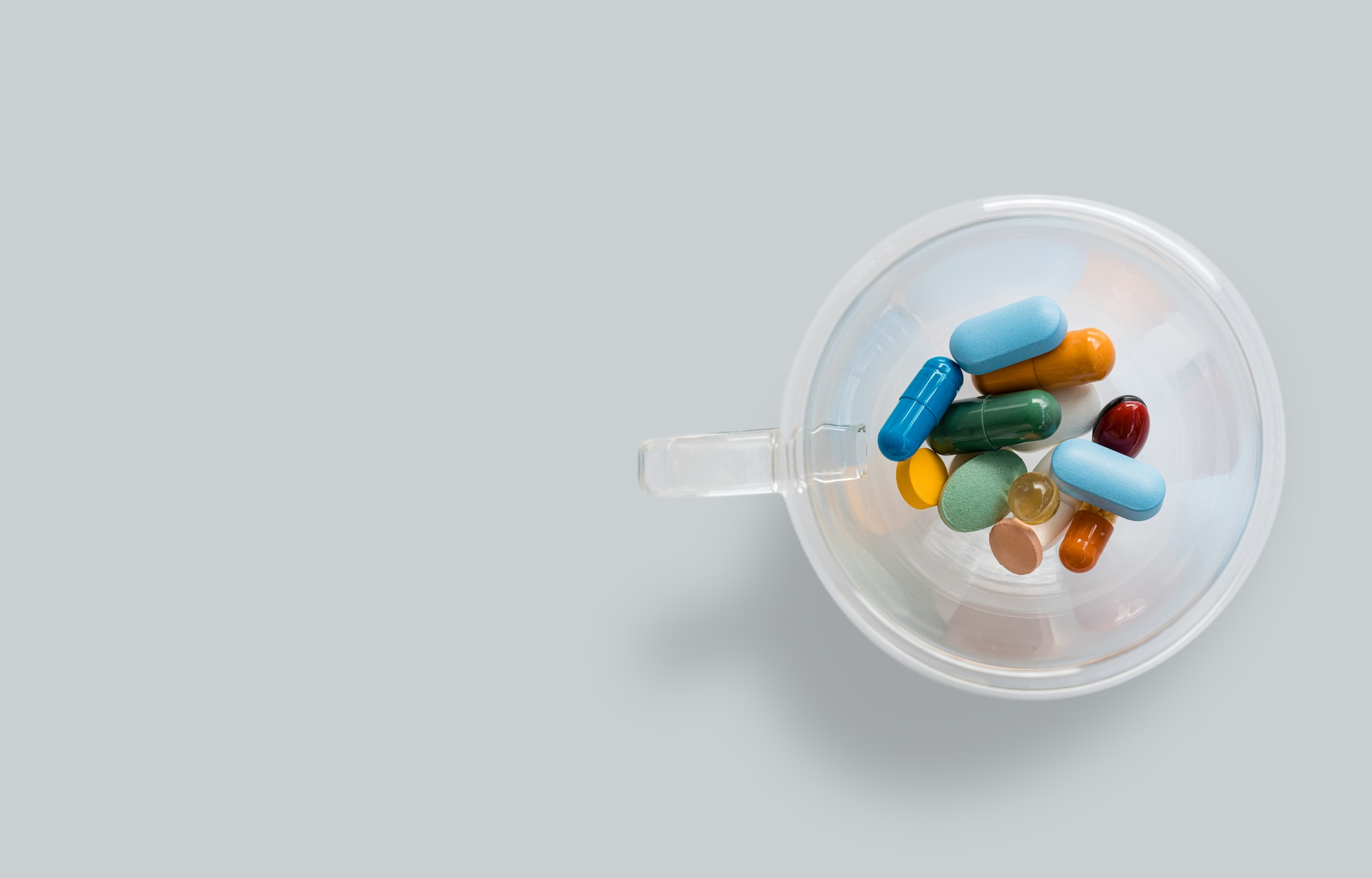 A transparent coffee cup with colourful pills on gray background. Dangerous virus. Virus epidemic concept. Tablets, Medicine and healthy. Close up of capsules. Differend kind of pills. Copy space