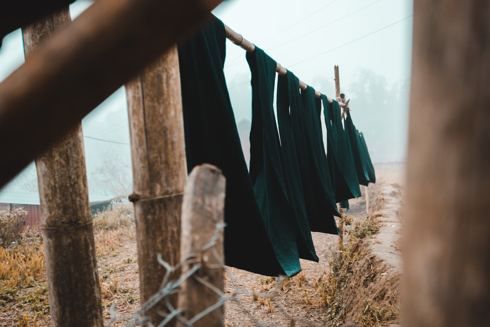 blue and black textiles hanging on wire fence during daytime