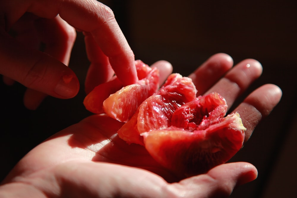 person holding red sliced fruit