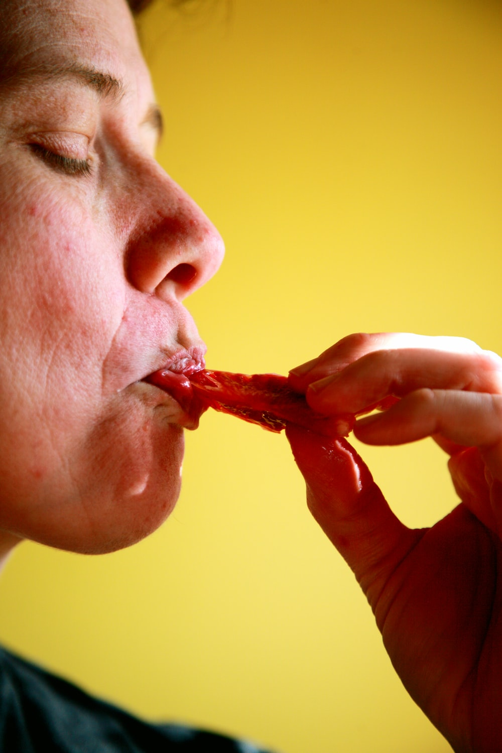 person eating red food in yellow room