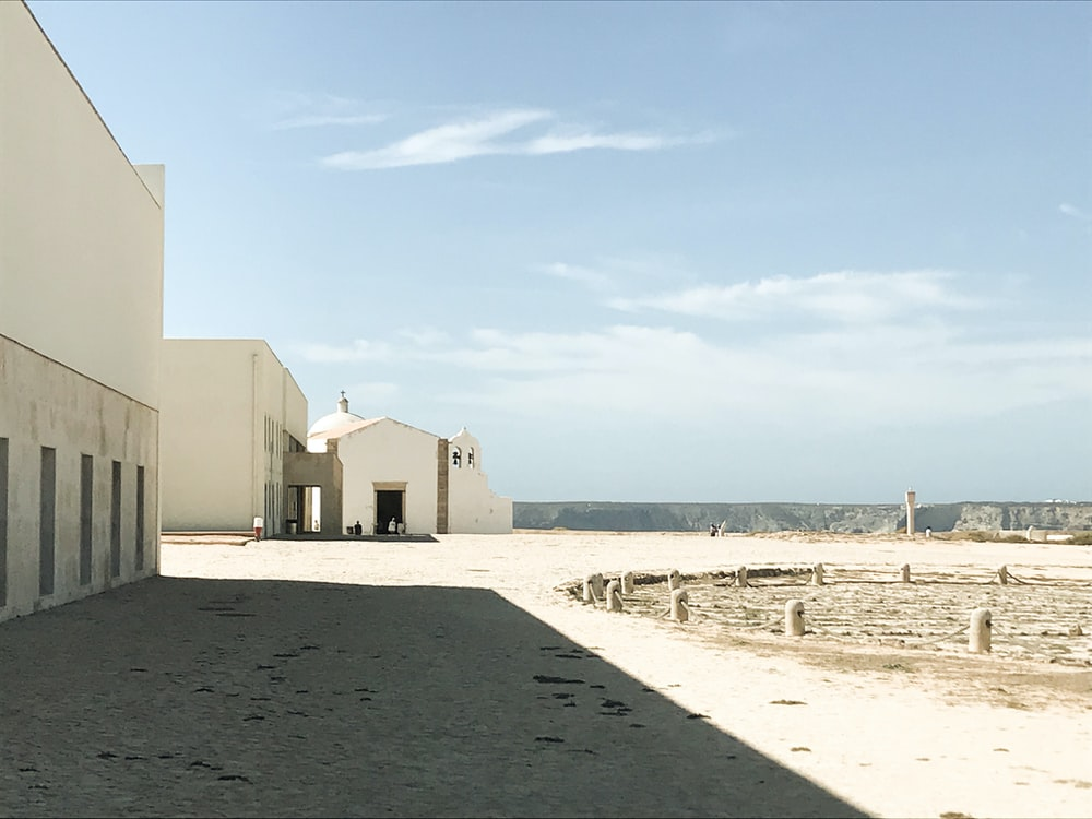 white concrete building near sea under blue sky during daytime