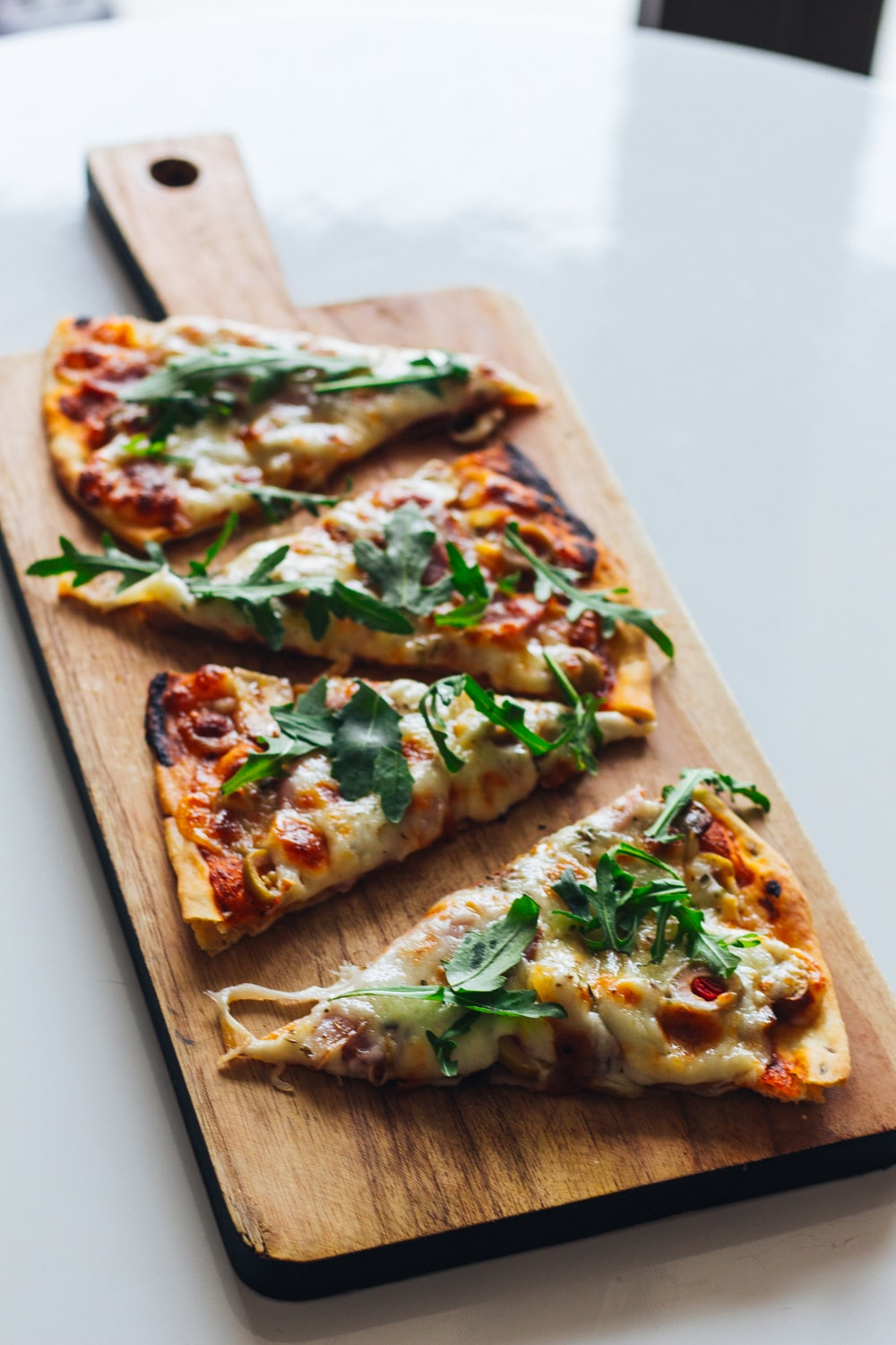 pizza with green leaf on brown wooden tray