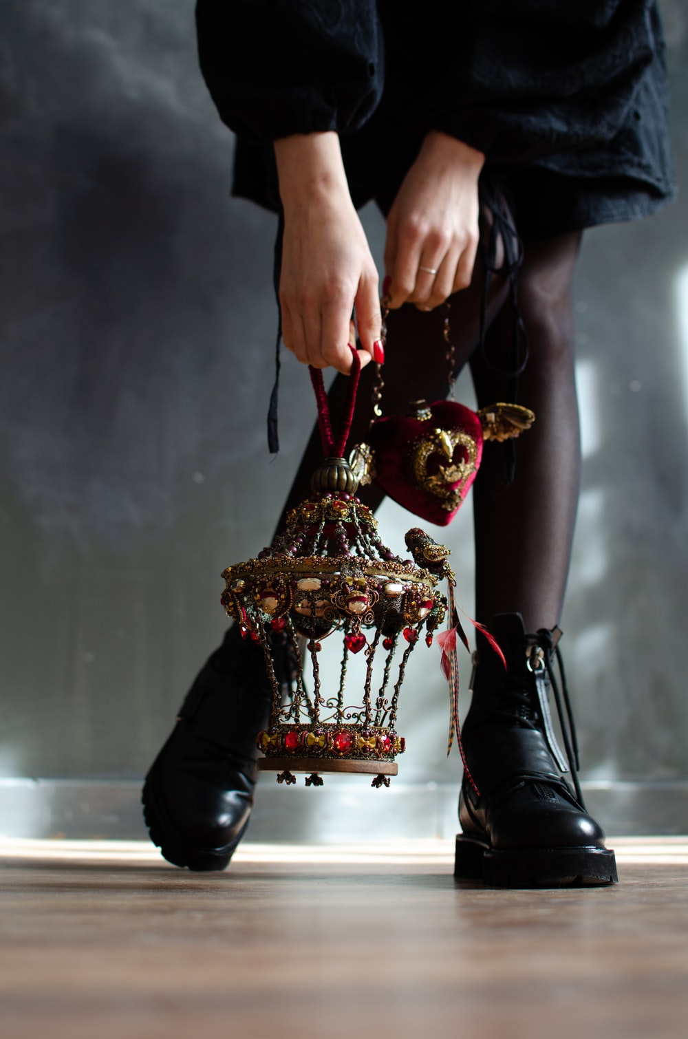 person in black leather boots holding gold trophy
