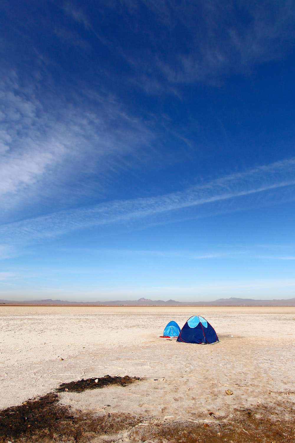 blue and white tent on brown sand under blue sky during daytime