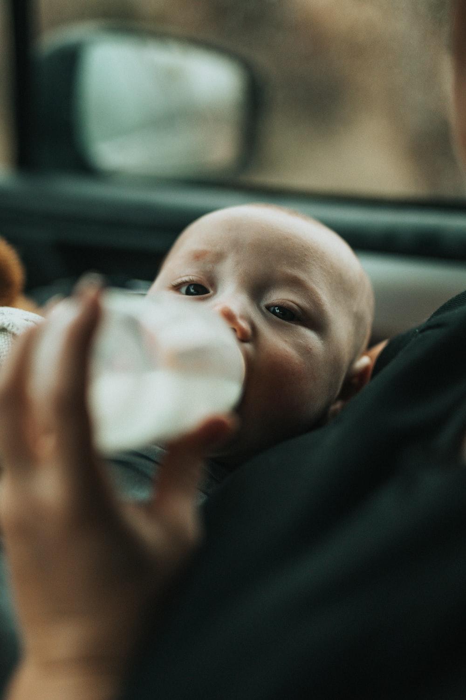 baby in blue shirt drinking milk from feeding bottle