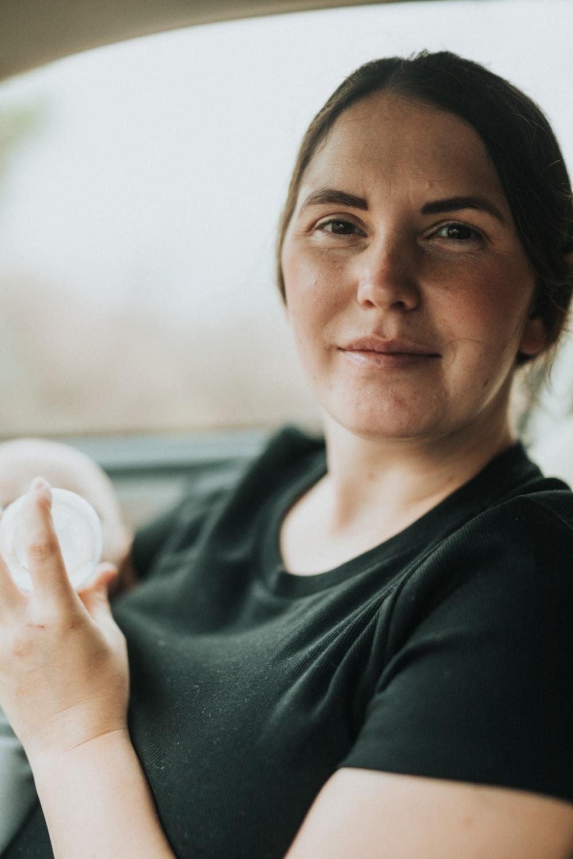 woman in black crew neck shirt holding white egg