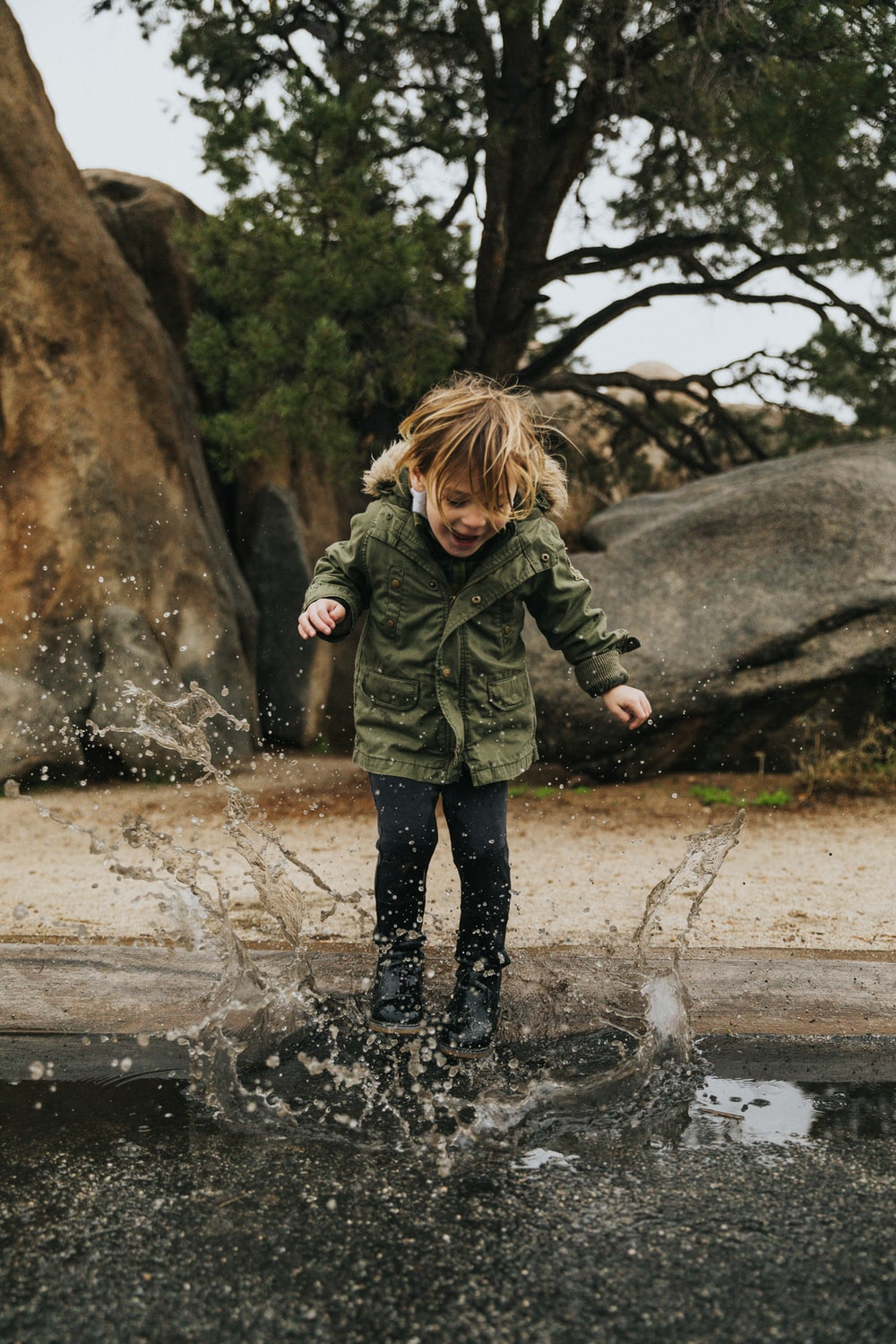 girl in green jacket standing on water