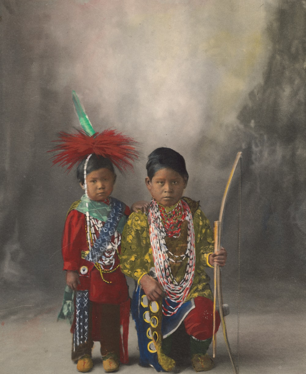 2 women in traditional dress holding stick