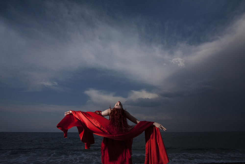 woman in red dress standing on sea shore under gray cloudy sky during daytime