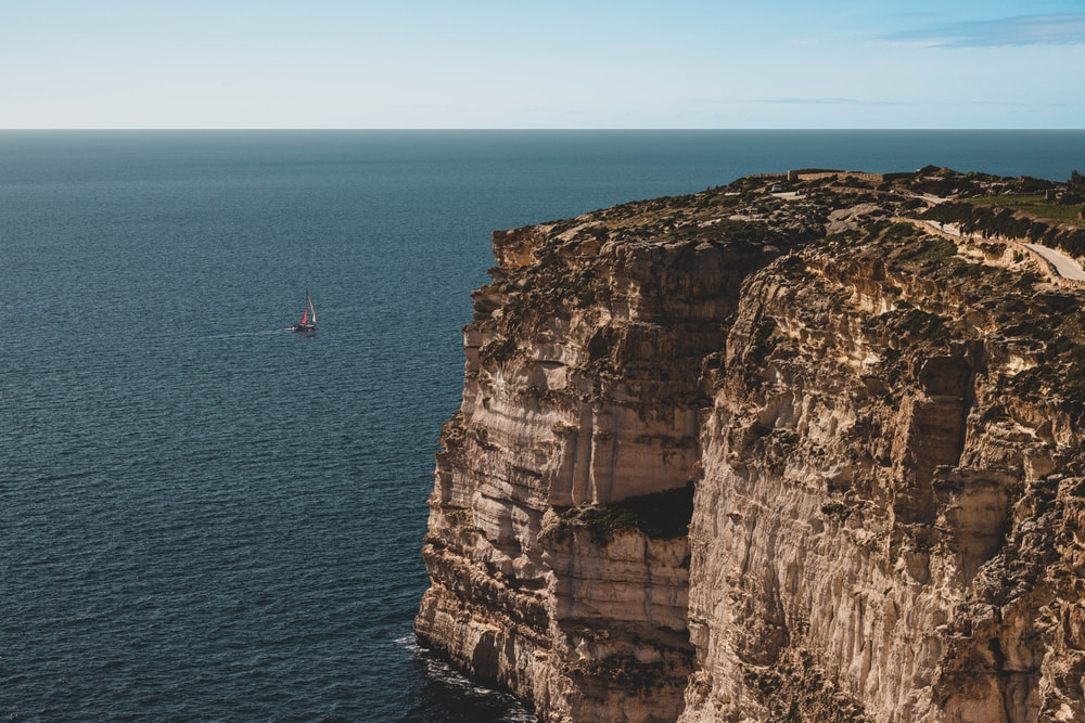 person in red shirt standing on cliff near body of water during daytime