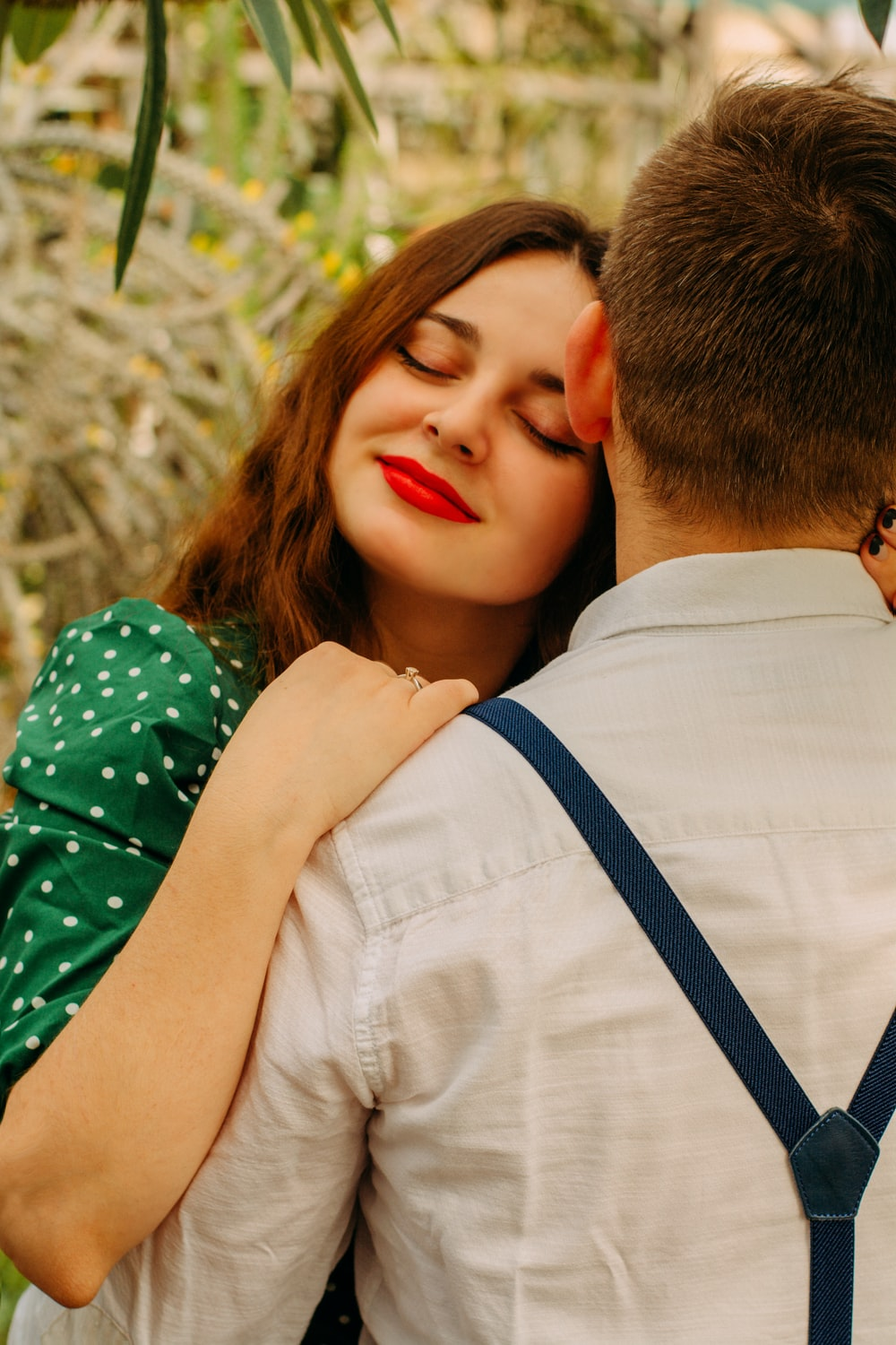 man in white dress shirt kissing woman in green and white floral dress