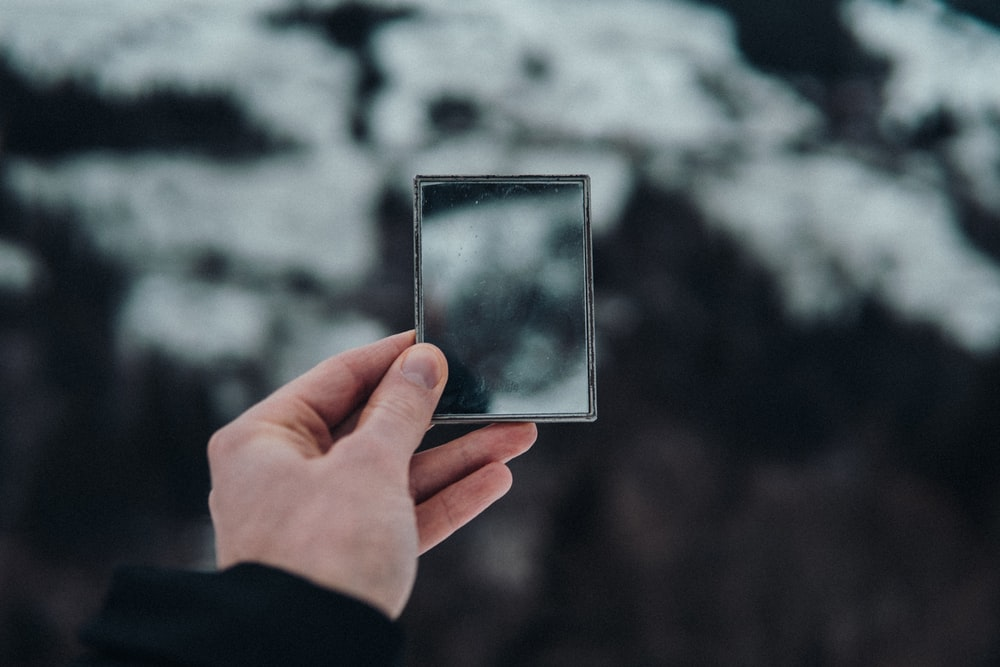 person holding silver square frame