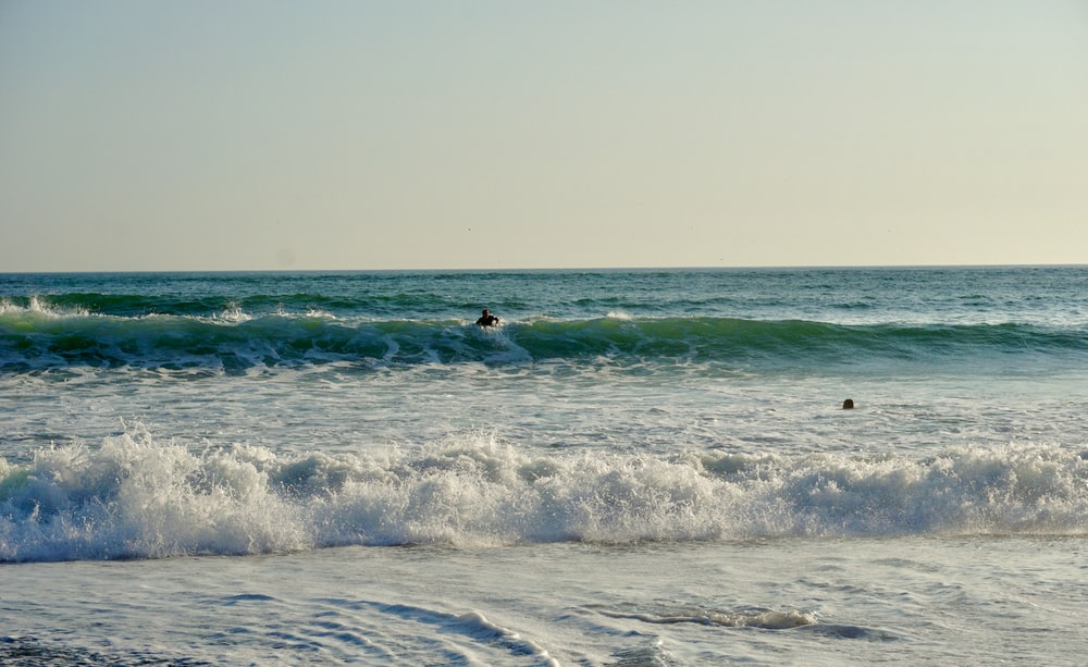 people surfing on sea waves during daytime