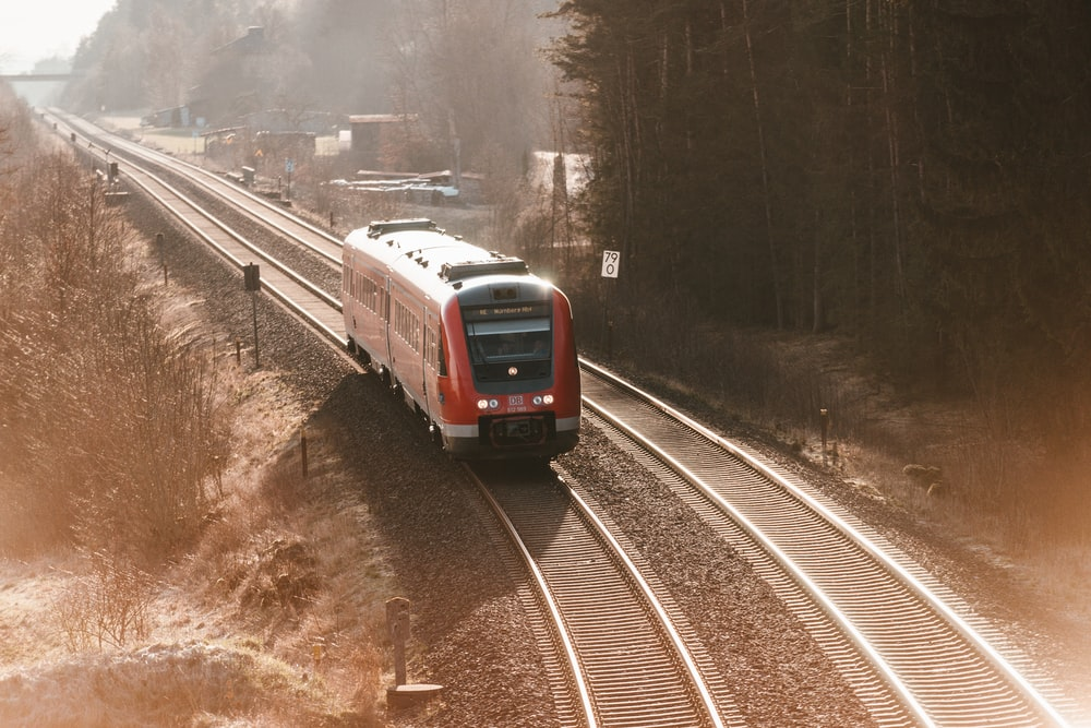 red and white train on rail road during daytime