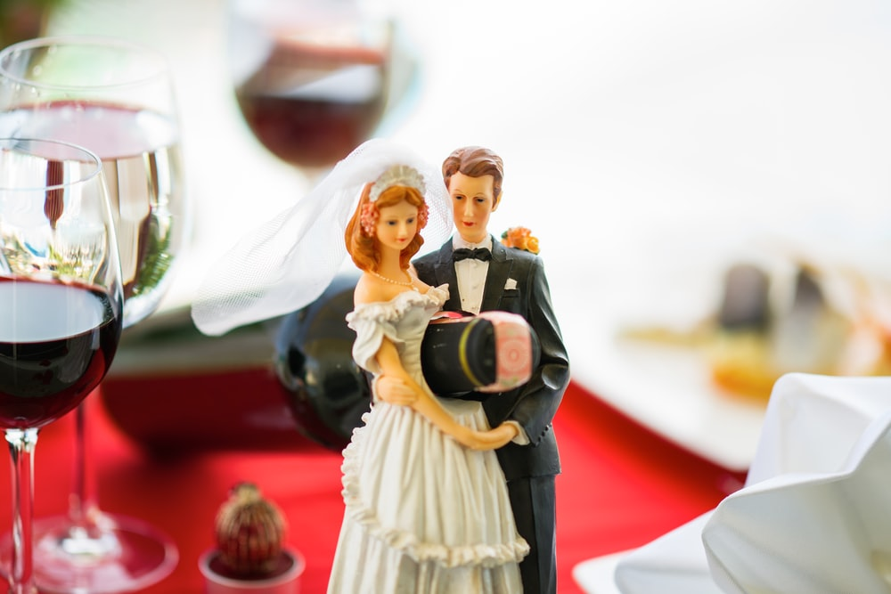 woman in white dress holding man in black suit figurine