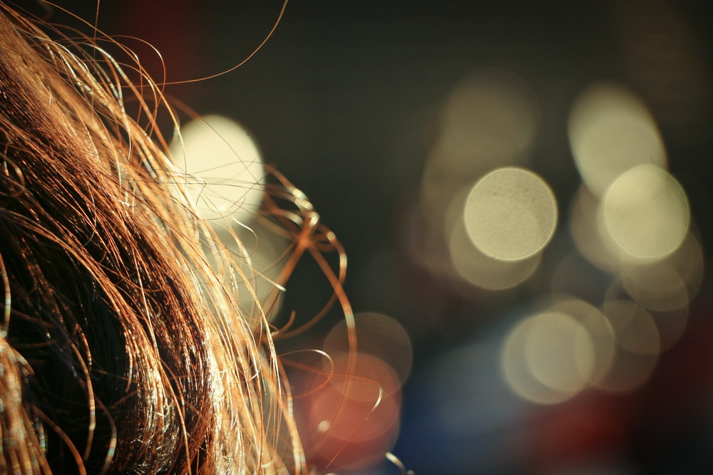 bokeh photography of womans brown hair