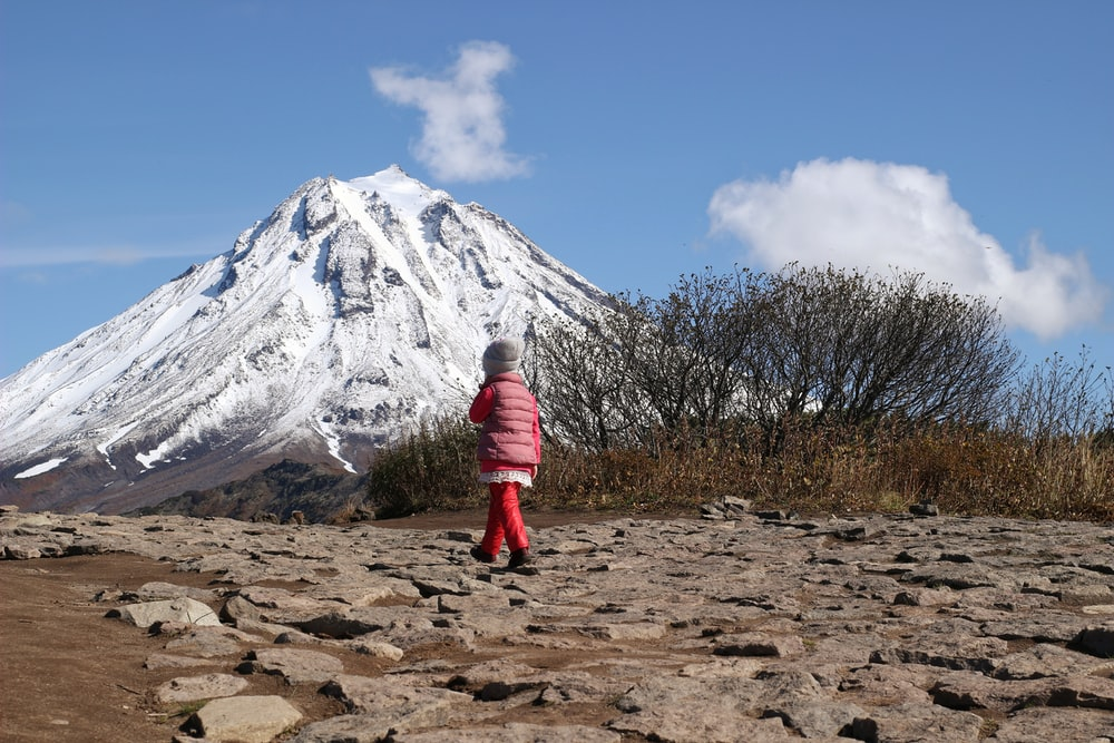 person in red jacket and red pants standing on brown field near snow covered mountain during