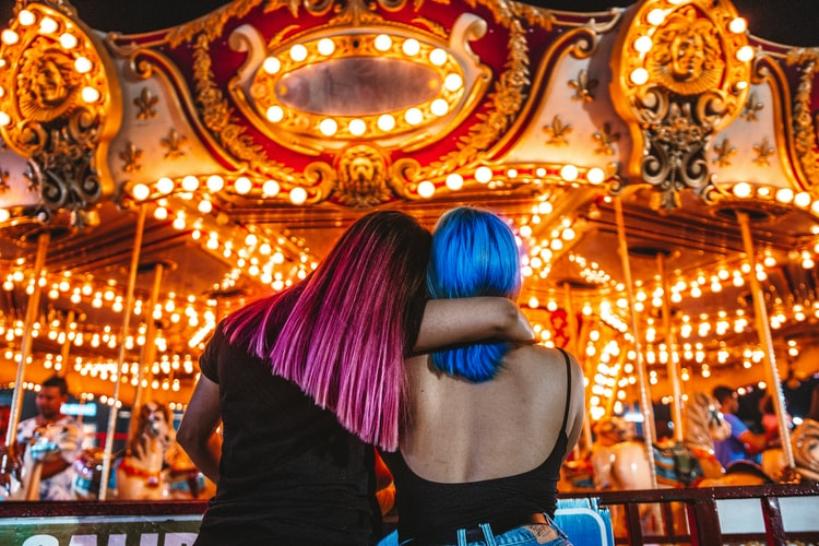 A photo of two girls from behind. They are sitting and looking at a bright carousel, one has her arm around the other. They have pink and blue hair. It's a warm picture of friendship and connection.