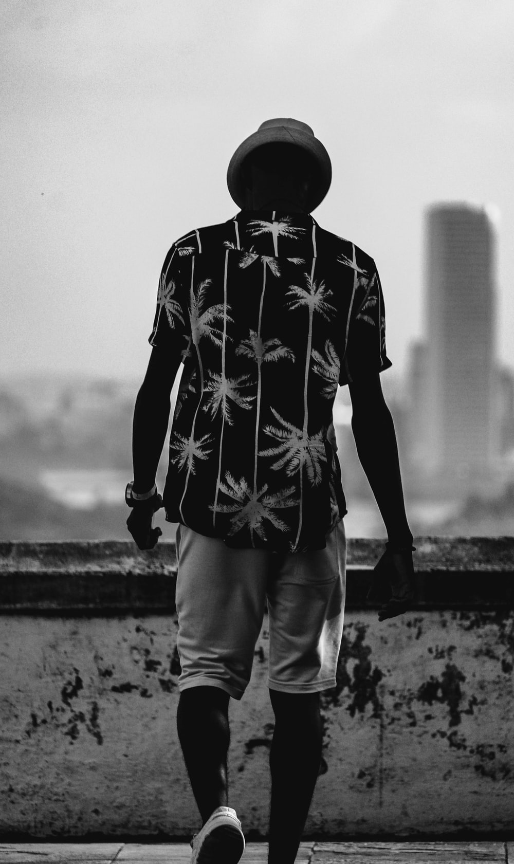 grayscale photo of man in black and white star print long sleeve shirt and white pants