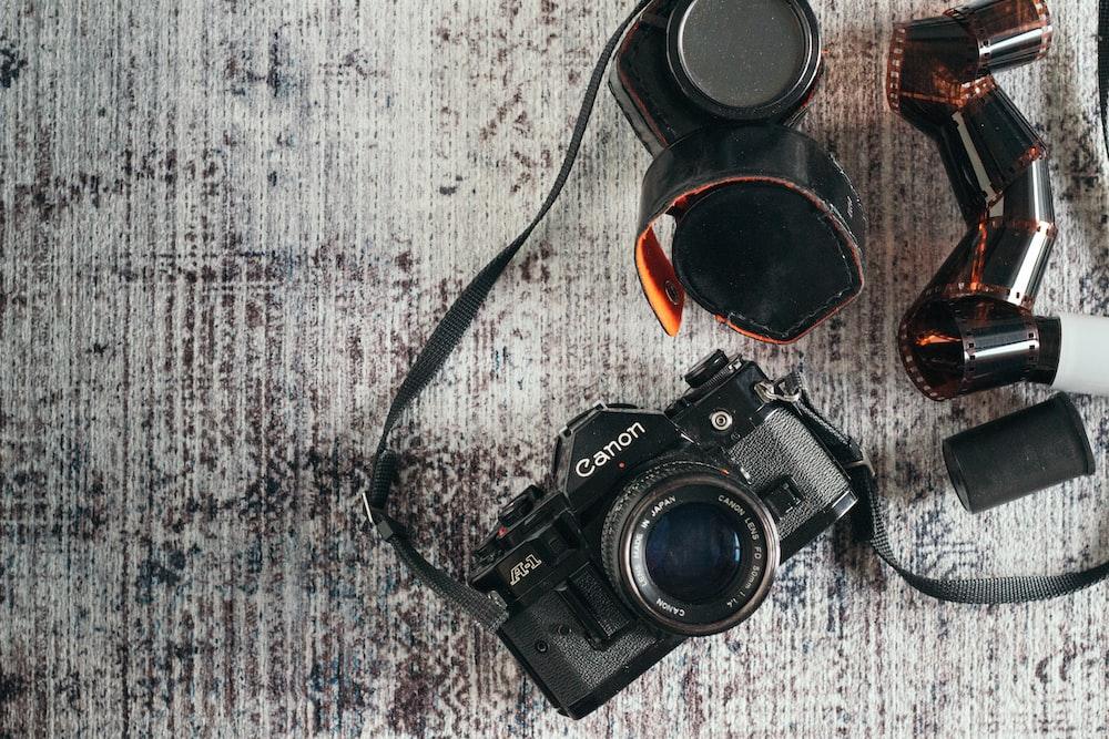 black nikon dslr camera on gray and white textile