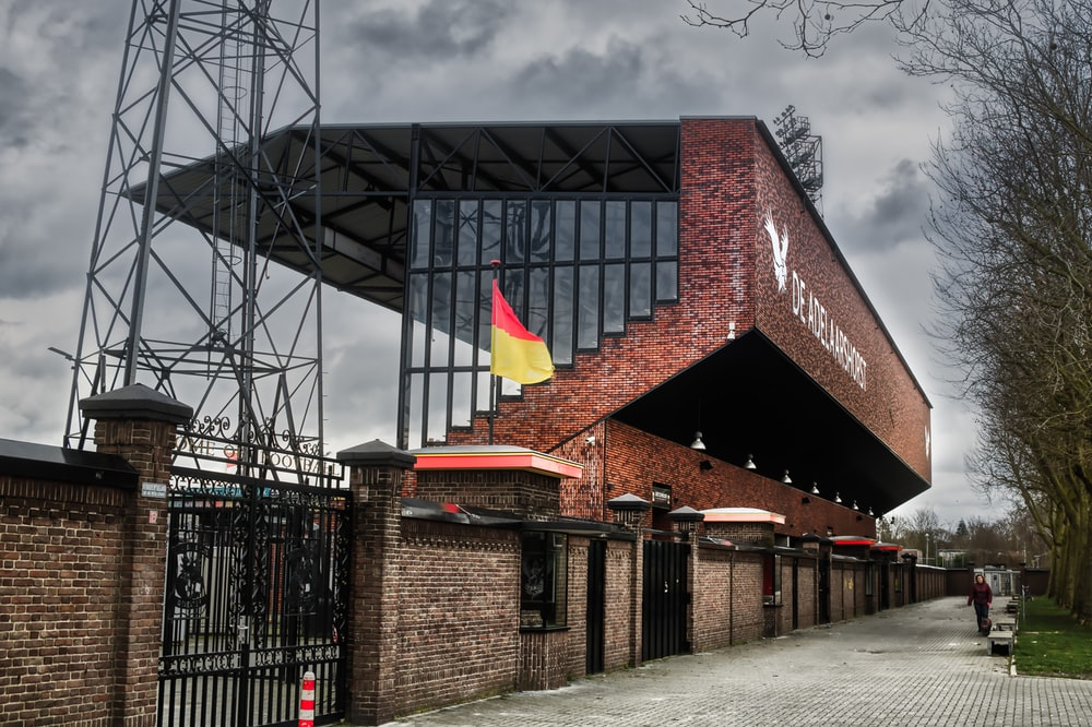 brown brick building with flags on roof under gray cloudy sky