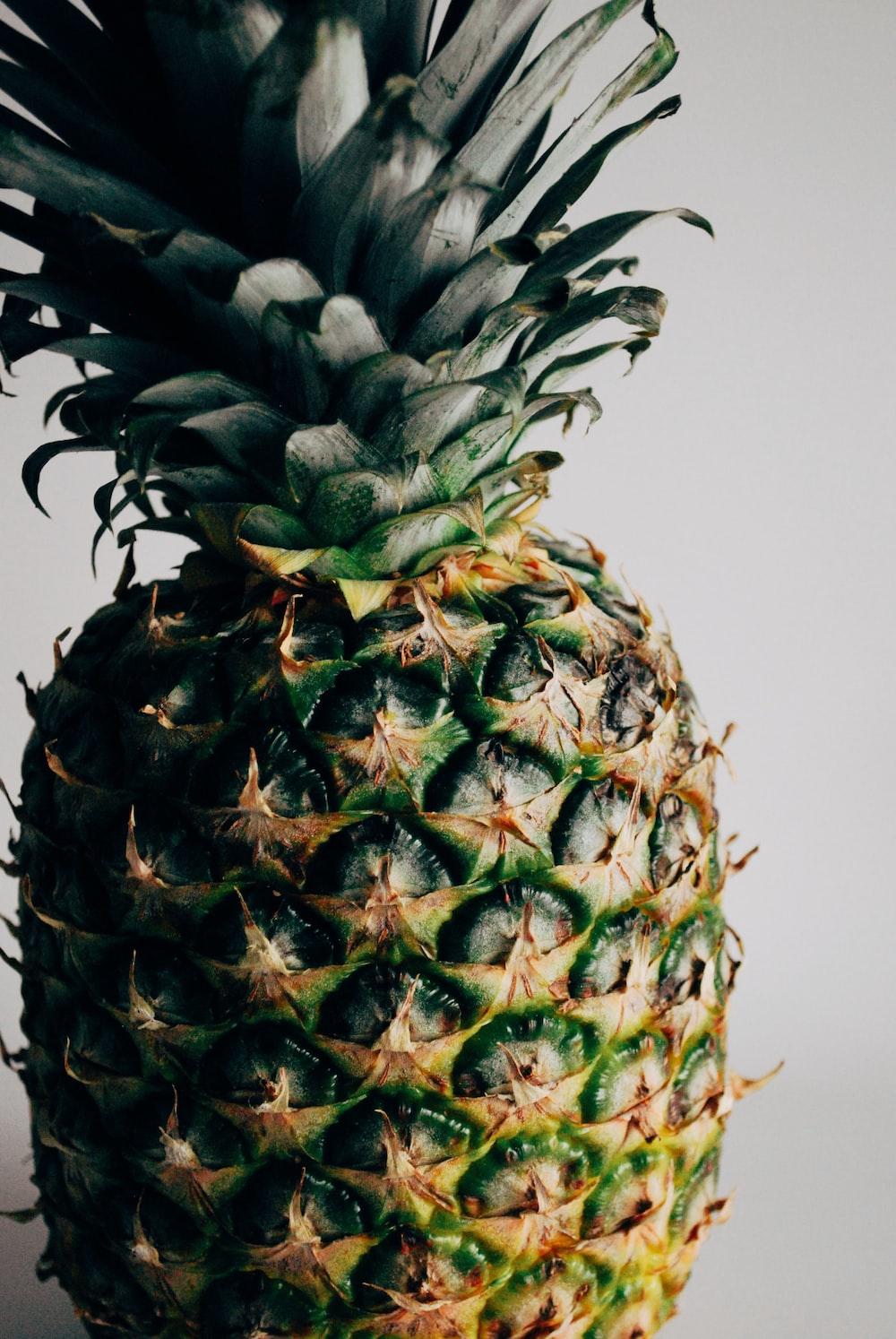 green pineapple fruit on white table