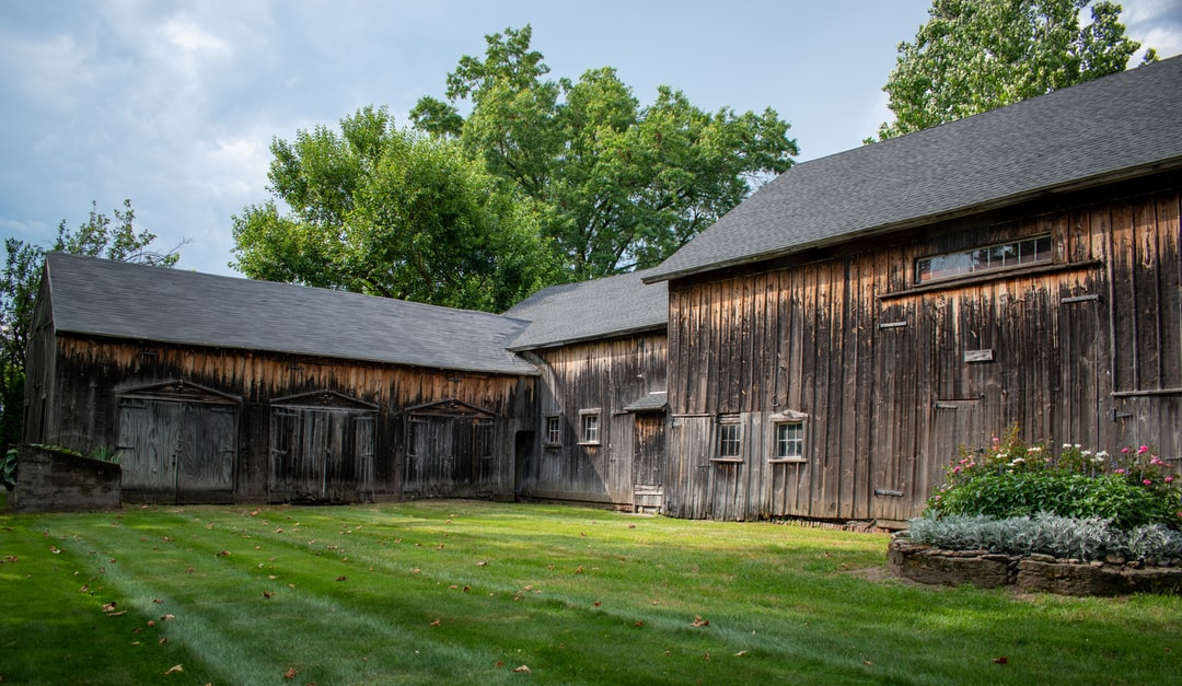 Rustic attached (expanded) barns with flower bed on manicured lawn