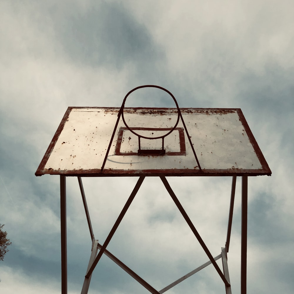 brown and black basketball hoop under white clouds