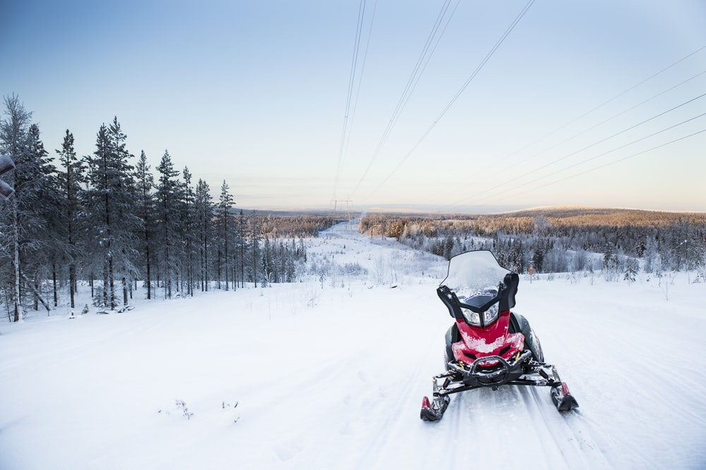 person riding snow mobile on snow covered field during daytime